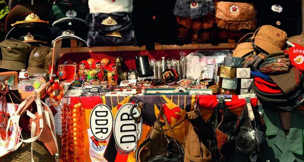 Tourist souvenirs, old DDR symbols and Soviet Russian uniforms for sale at stall next to Checkpoint Charlie. Image: Alamy