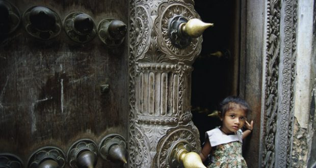 Curious onlooker in an ornate doorway, Stone Town. Image: Getty