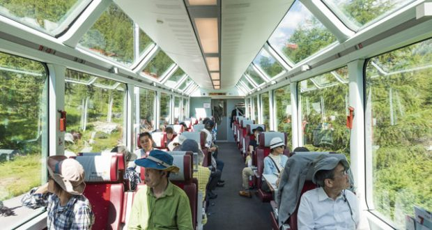 Passengers taking in the view through the Glacier Express train's iconic panoramic windows. Image: Slawek Kozdras