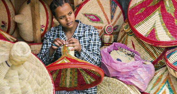 A young woman makes traditional Ethiopian hand-woven baskets, used for serving injera flatbreads, on sale in Mercato Market. Image: AWL